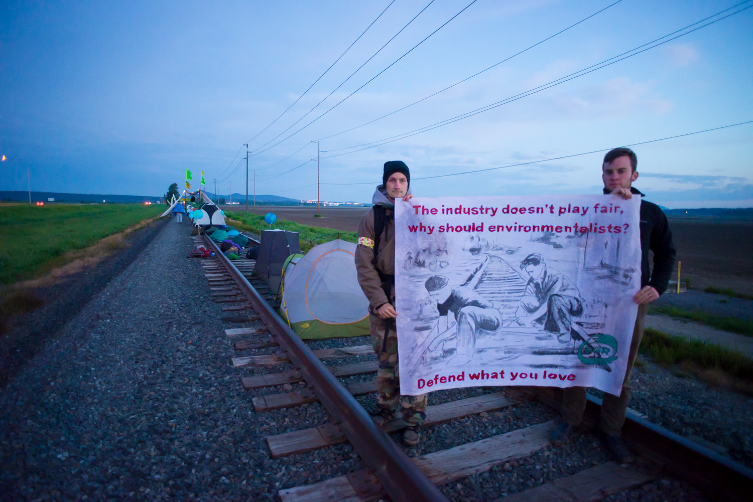 Holding a banner at the train blockade; banner advocates for sabotage.